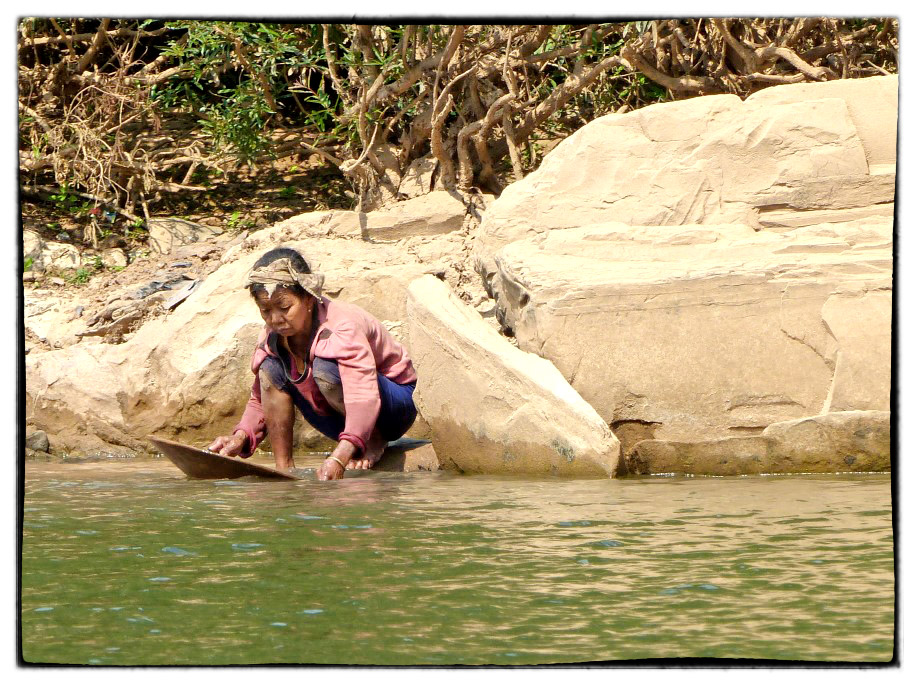 Woman crouching by a river panning for gold