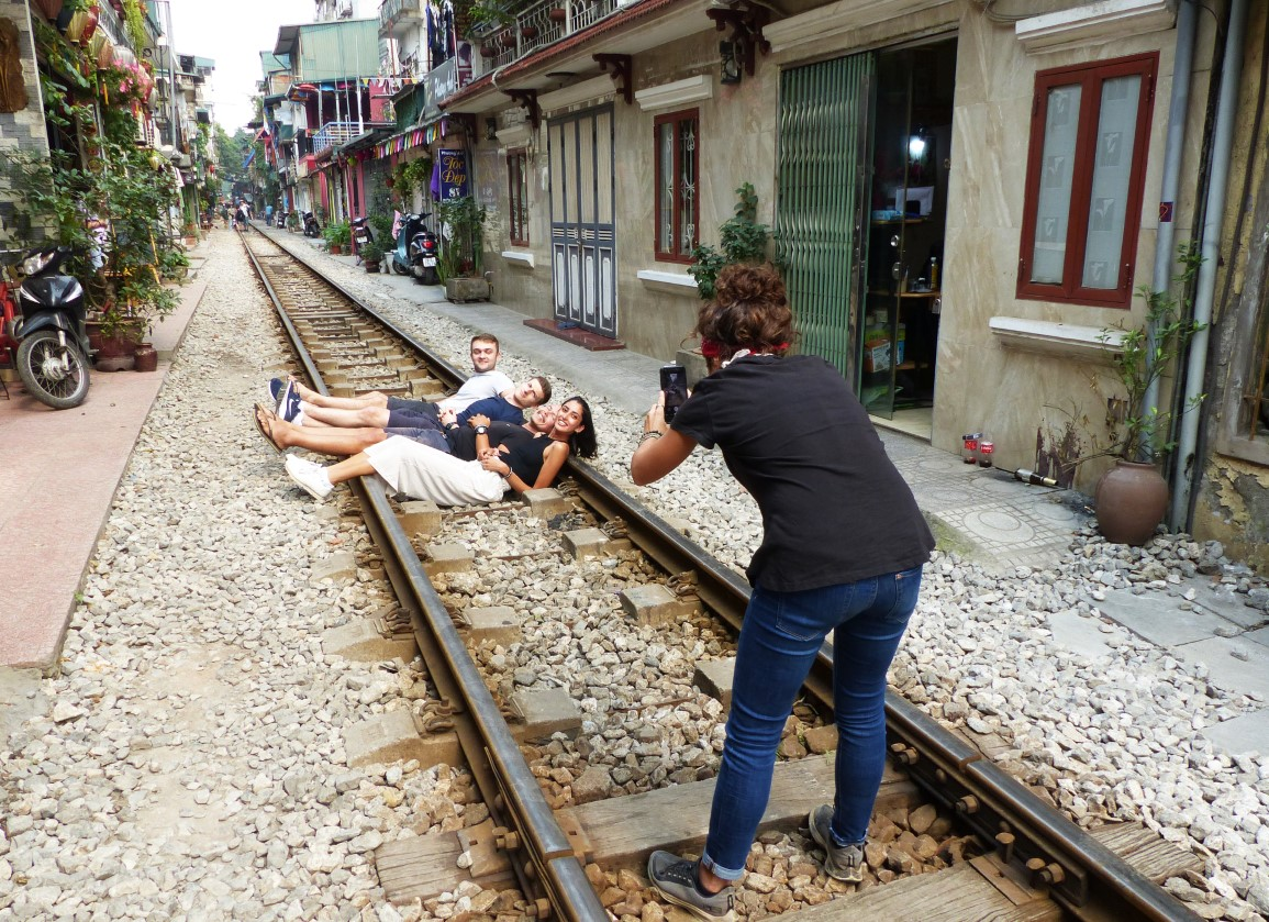 Young people posing for photos lying on the train track