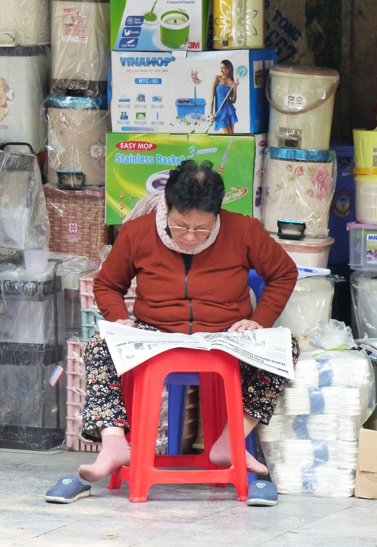 Lady reading a newspaper outside a shop