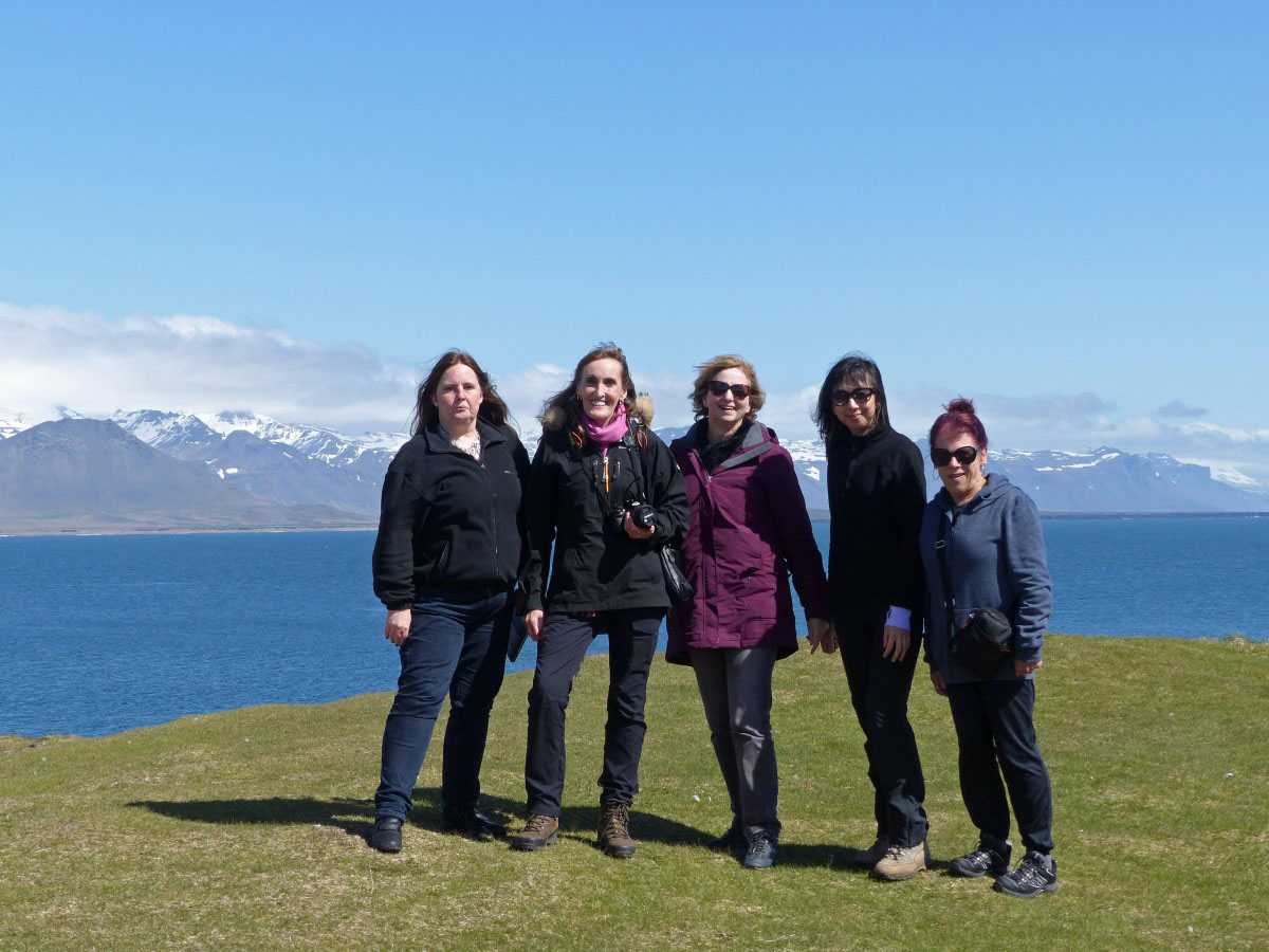 Five women on a cliff with mountains behind