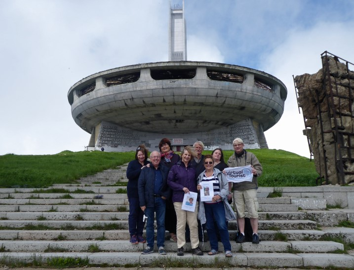 Group of people in front of decaying Communist structure