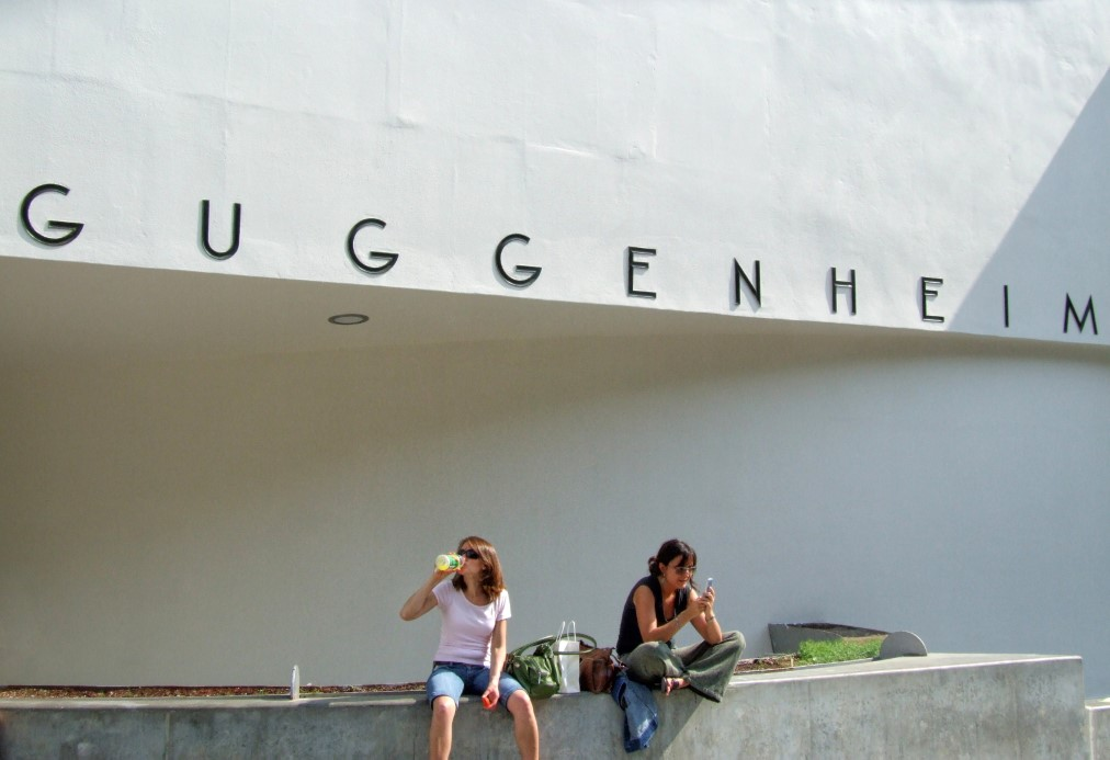 Two girls picnicking with white wall behind