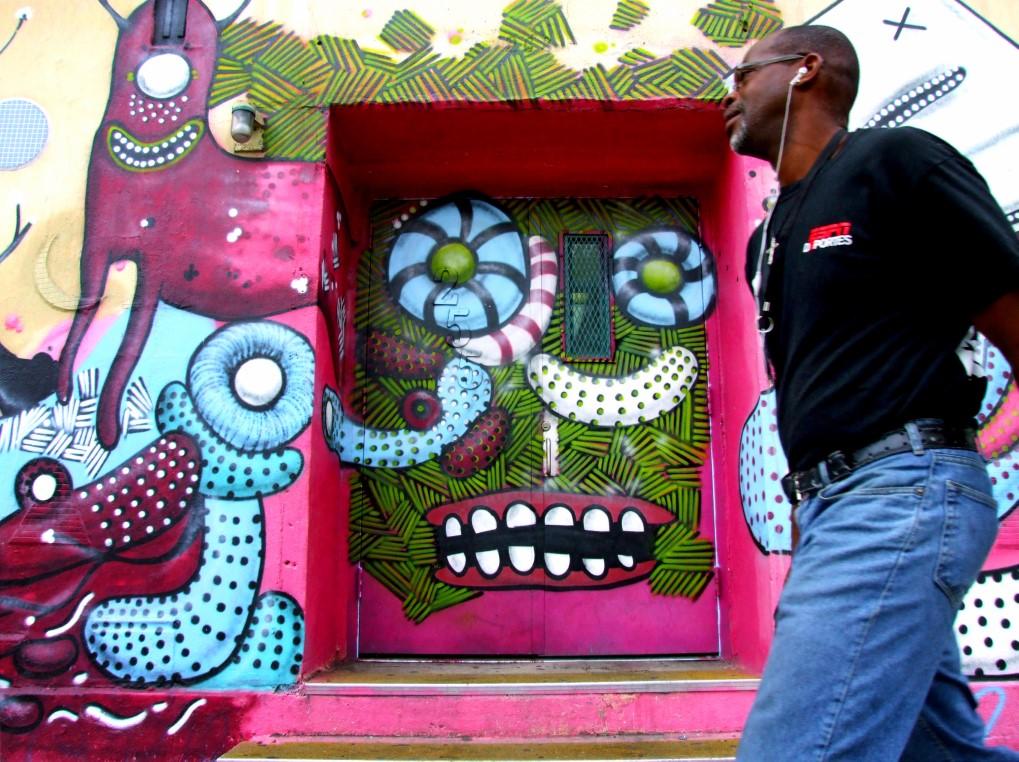 Man walking past bright street art