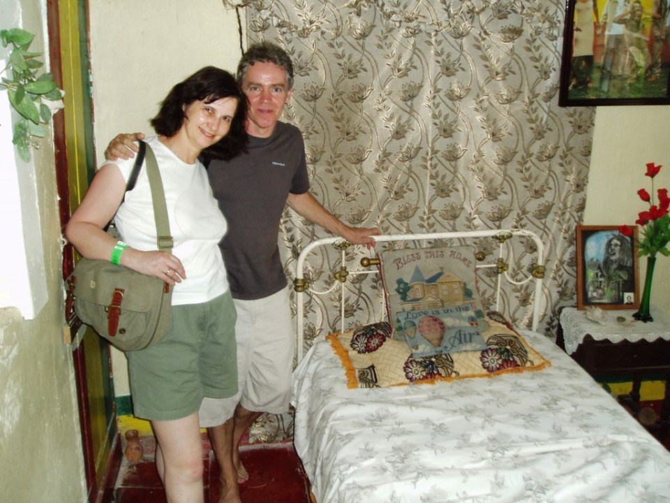 Two people standing by a metal frame bed