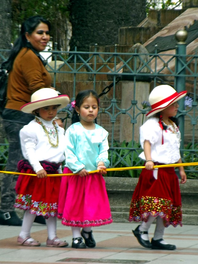 Little girls in white blouses and red skirts