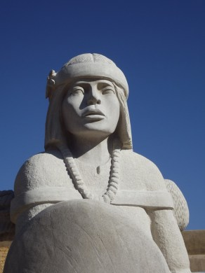 Large stone carving of woman in traditional headdress and beads