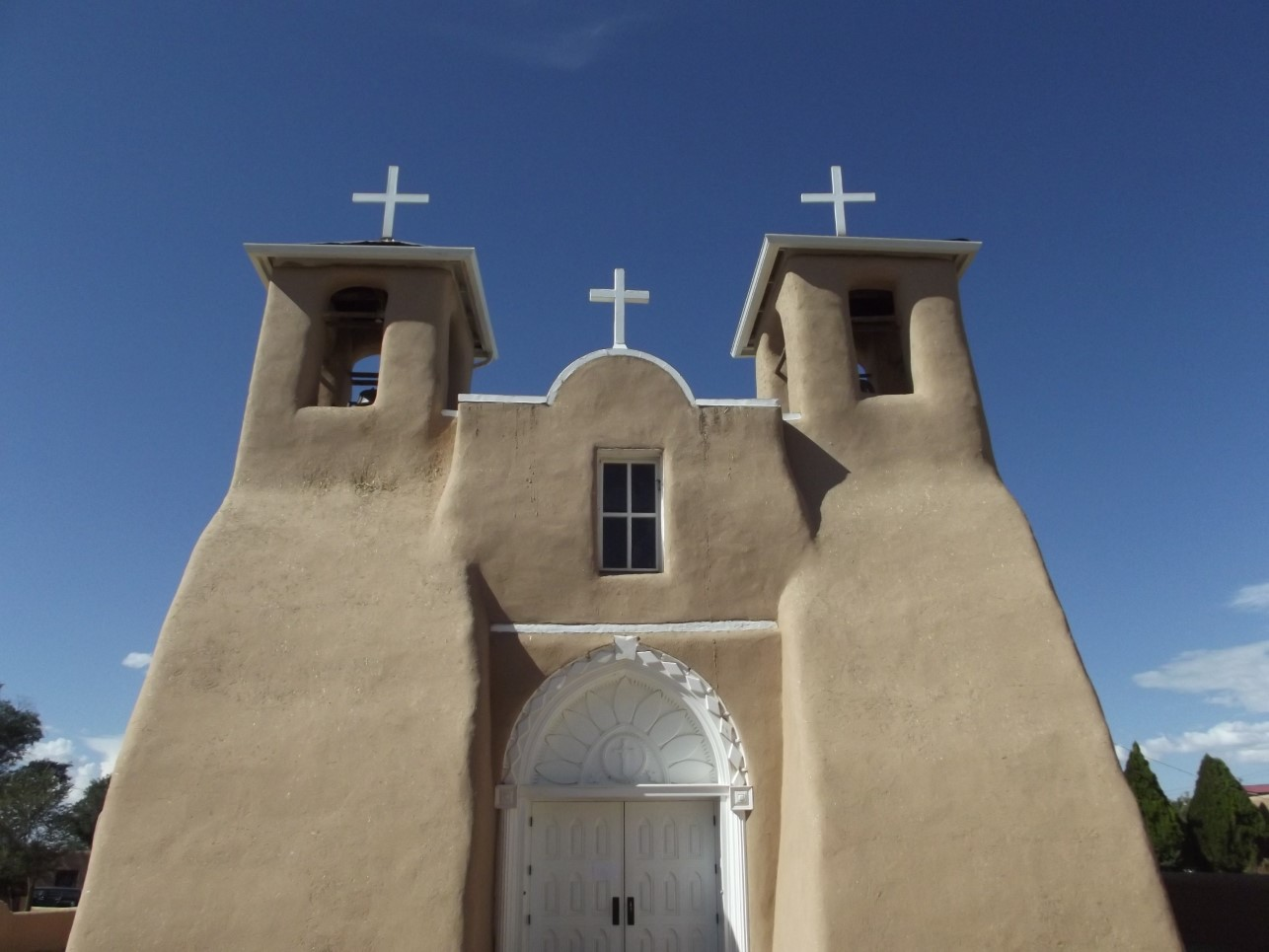 Solid adobe church with white crosses and door