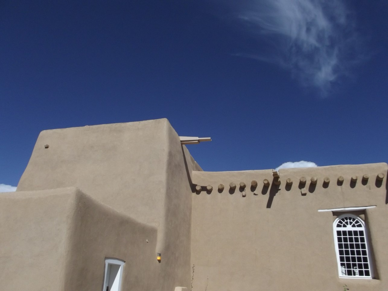 Adobe building with white window frames