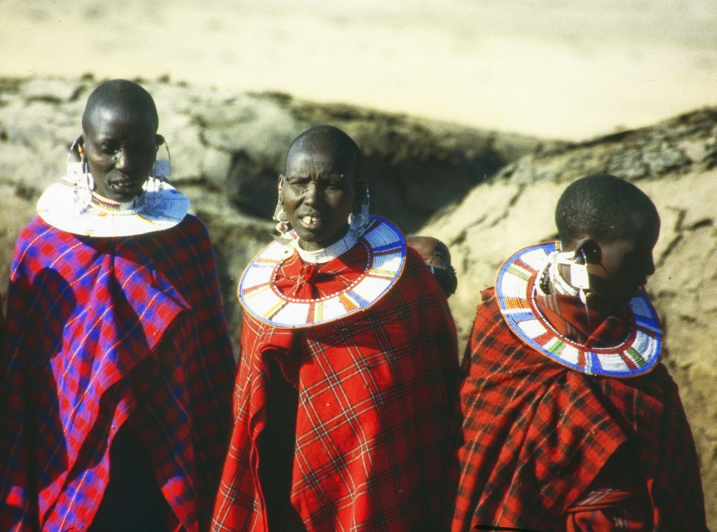 Three women in red checked fabric wraps