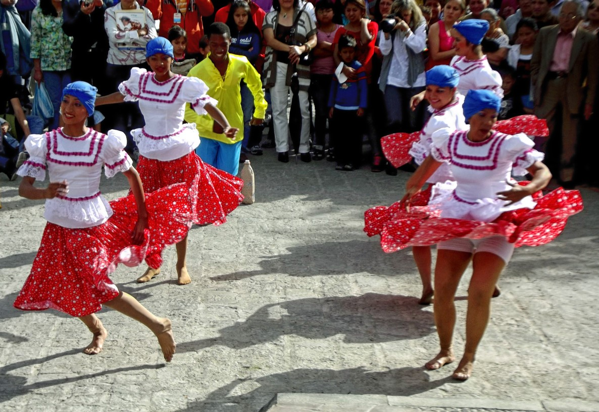 Ladies dancing in red skirts and white blouses