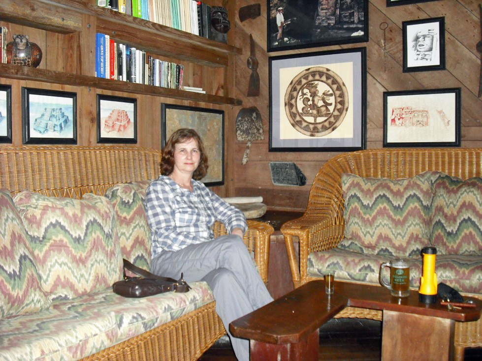 Woman sitting on a couch with wooden table and pictures on the wall