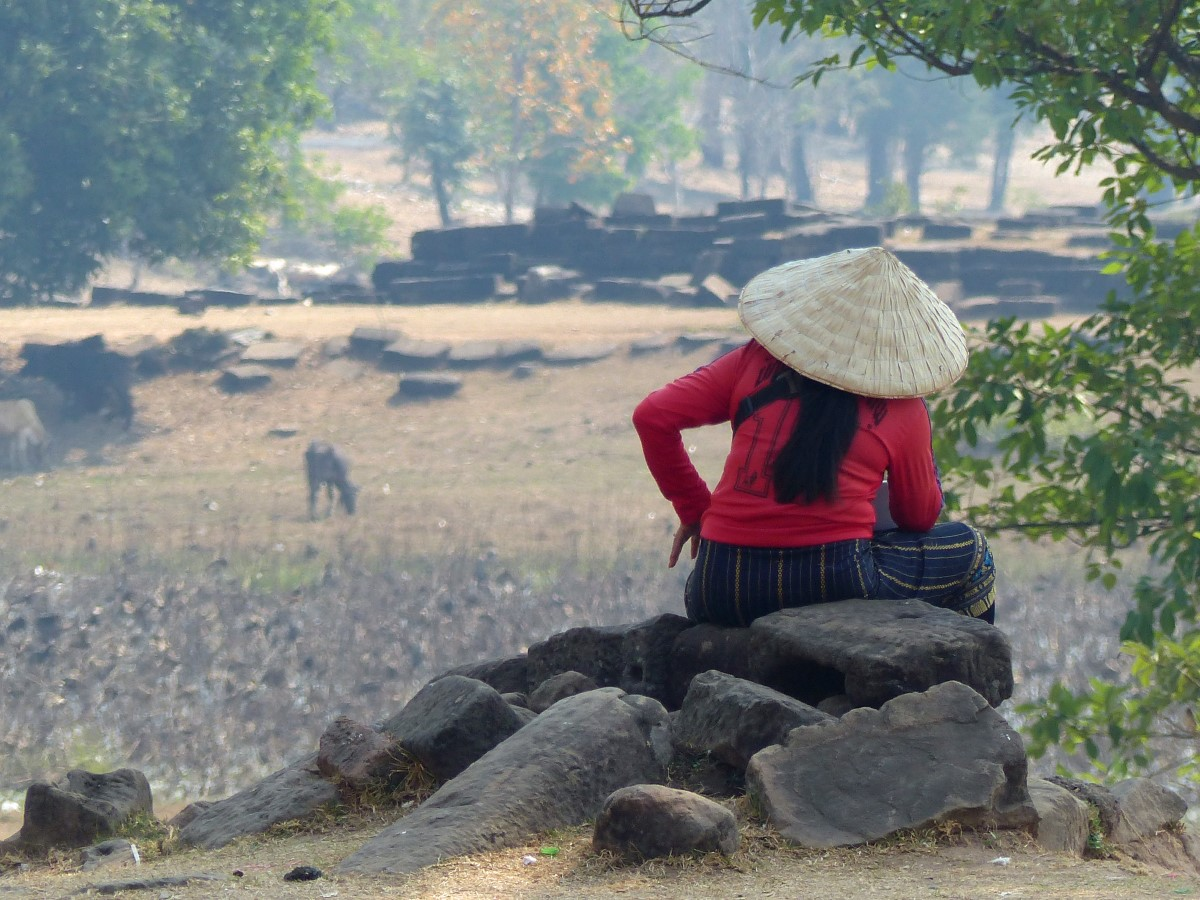 Lady in red top and large hat sitting among ruins