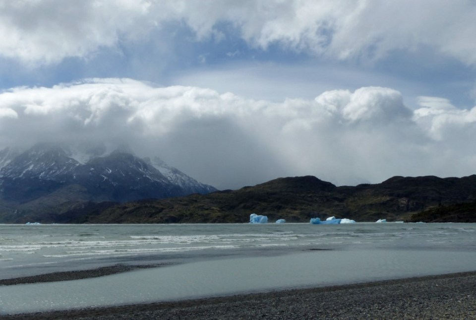 View of beach with icebergs and mountains beyond