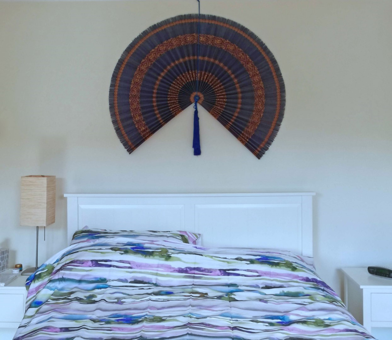 Large fan hung above a bed