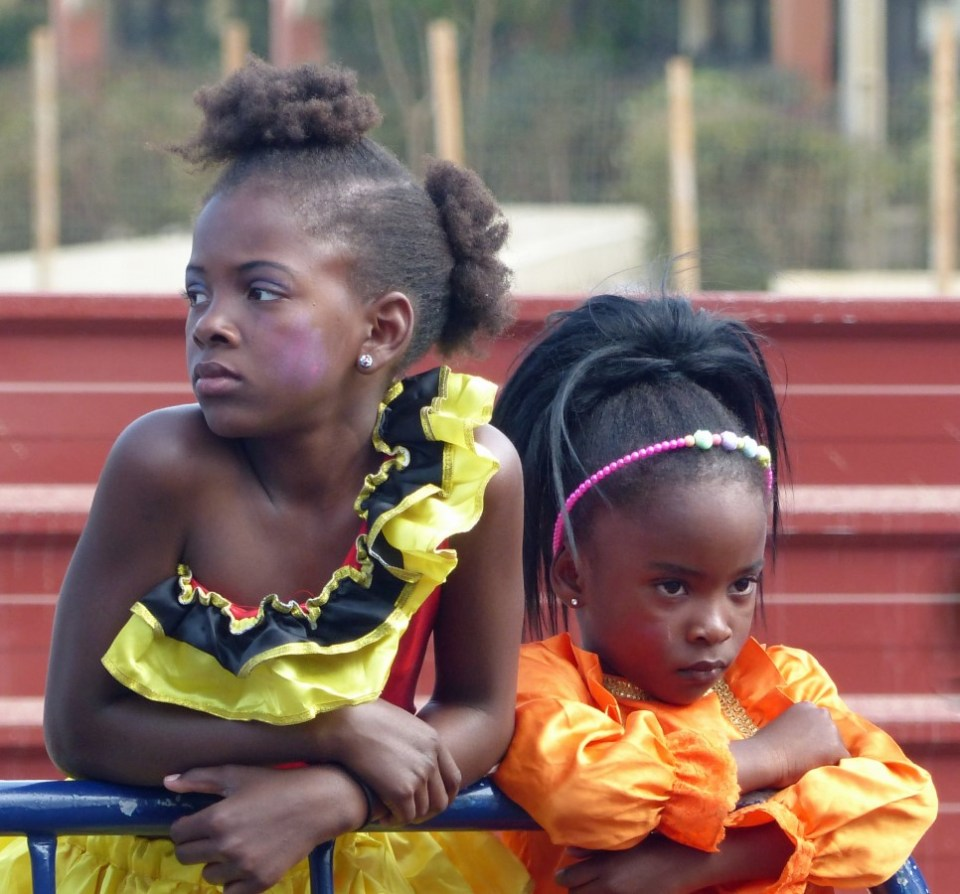 Two little girls leaning on a railing