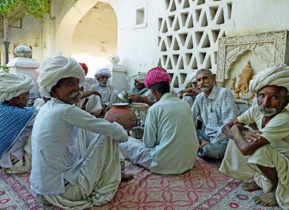 Men in Indian dress sitting on rugs