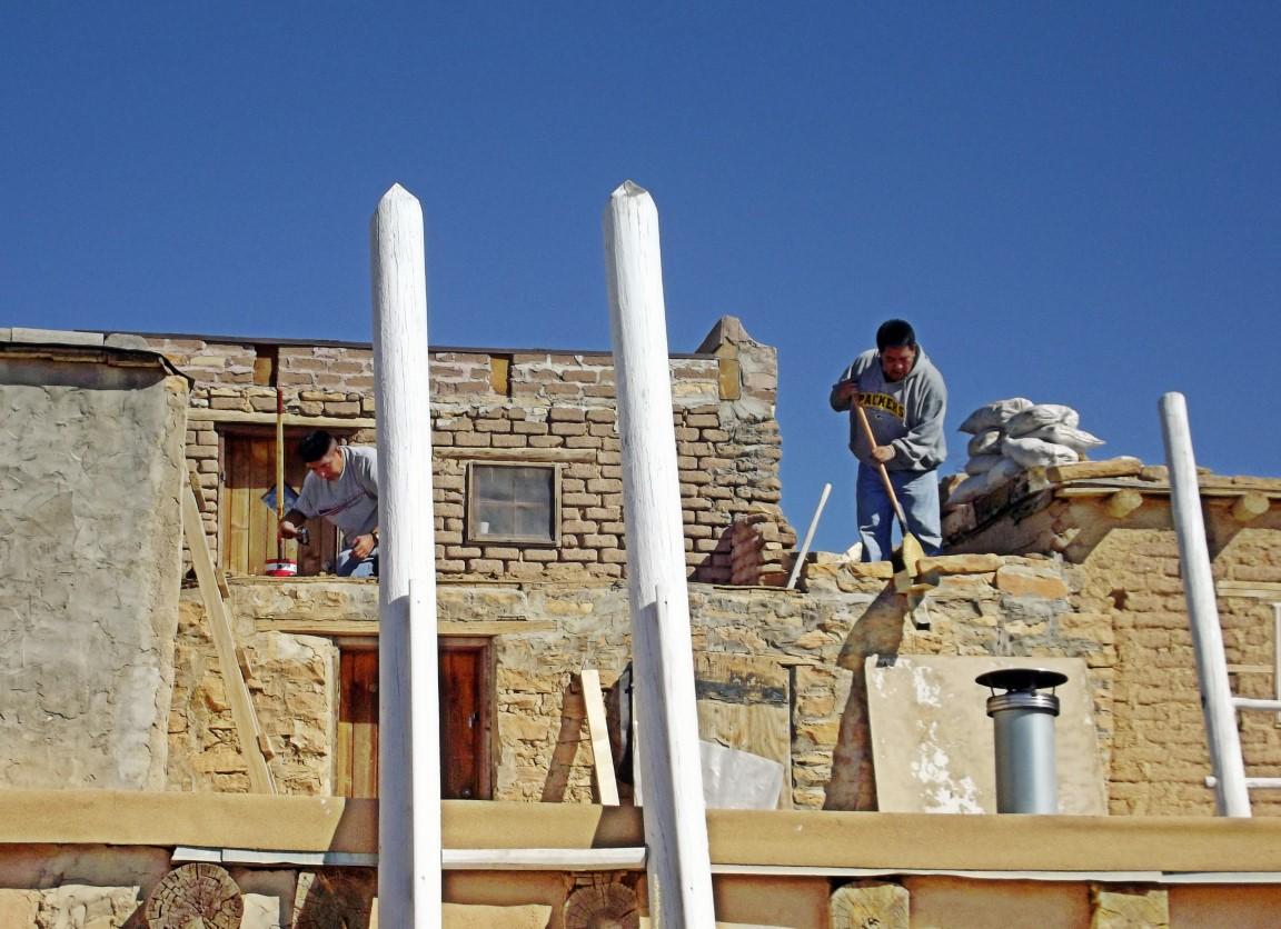 Men repairing adobe house