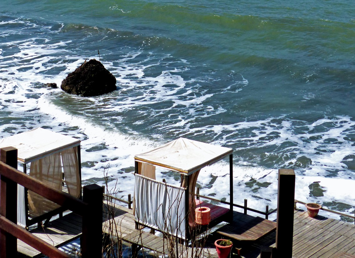 Looking down at decking by a rocky coastline