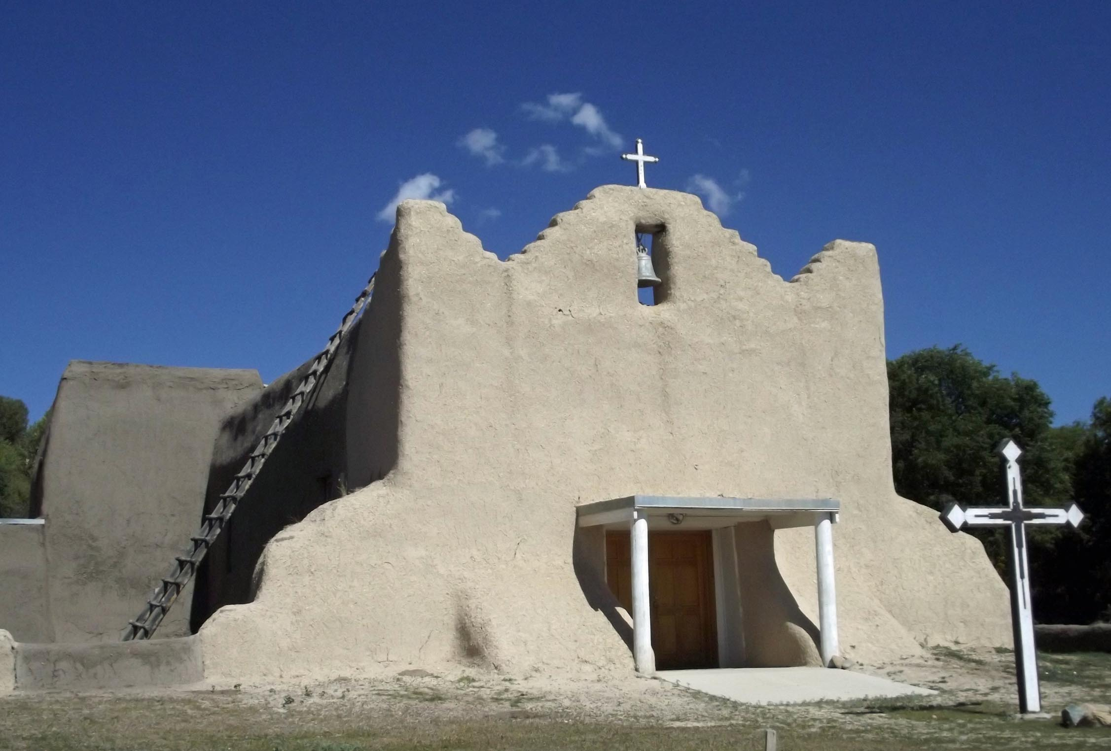 Adobe church with white cross in front