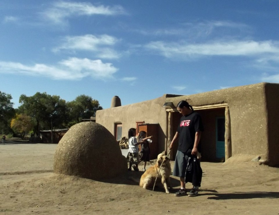 Adobe oven and house with mother and children