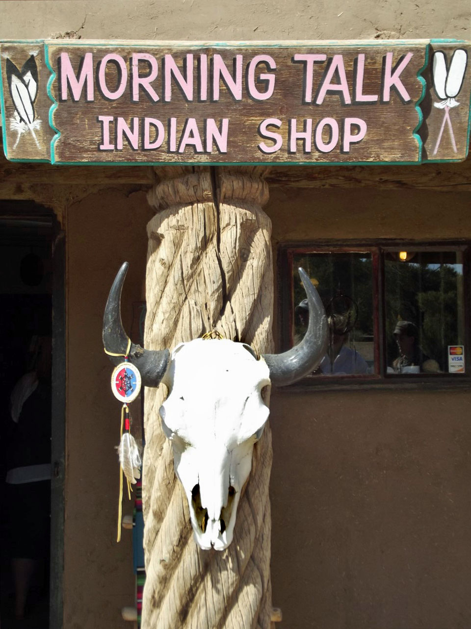 Cow's skull on wall under shop sign