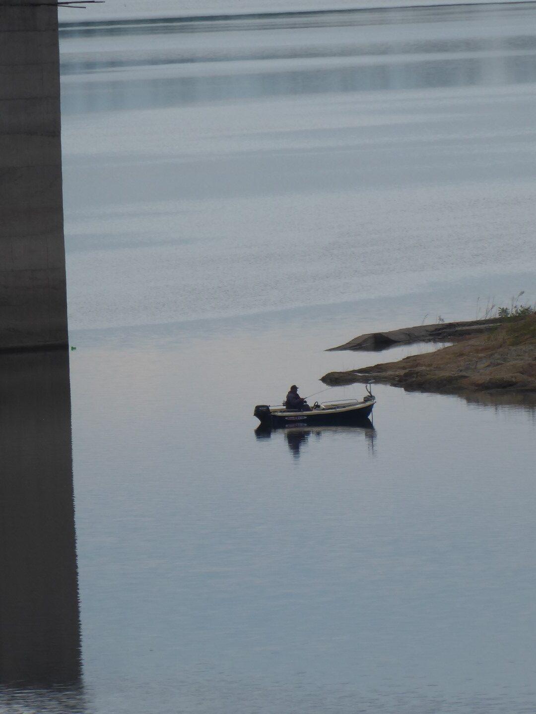 Fisherman in small motor boat near the shore