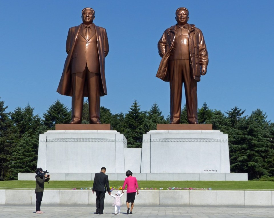 Large statues of North Korean Leaders with family approaching