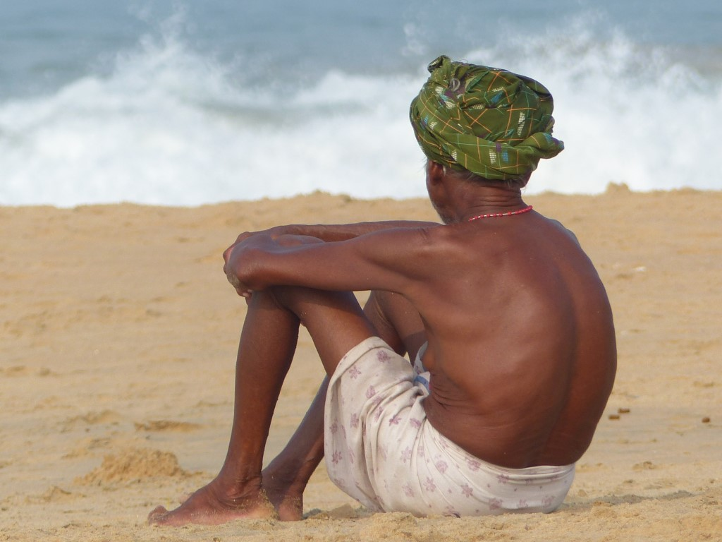 Man in a turban and sarong looking out to sea