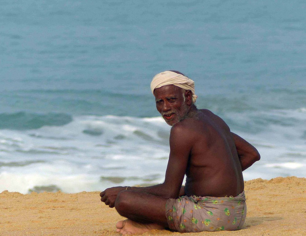 Man in white turban sitting on a beach