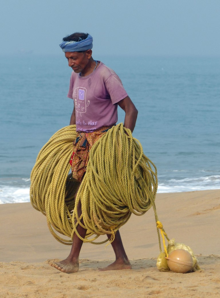 Man carrying lots of rope by the sea