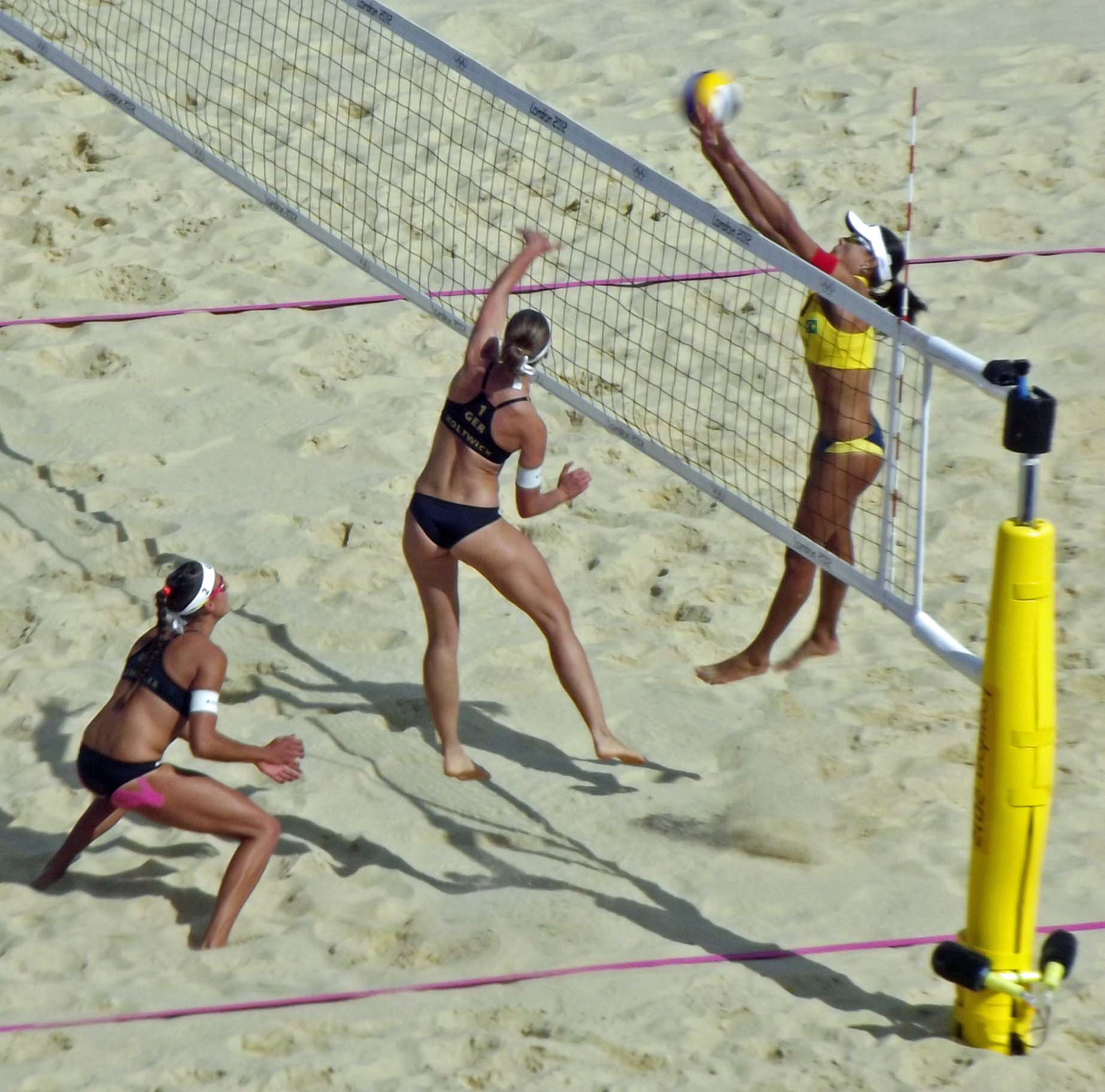 Three women playing beach volleyball