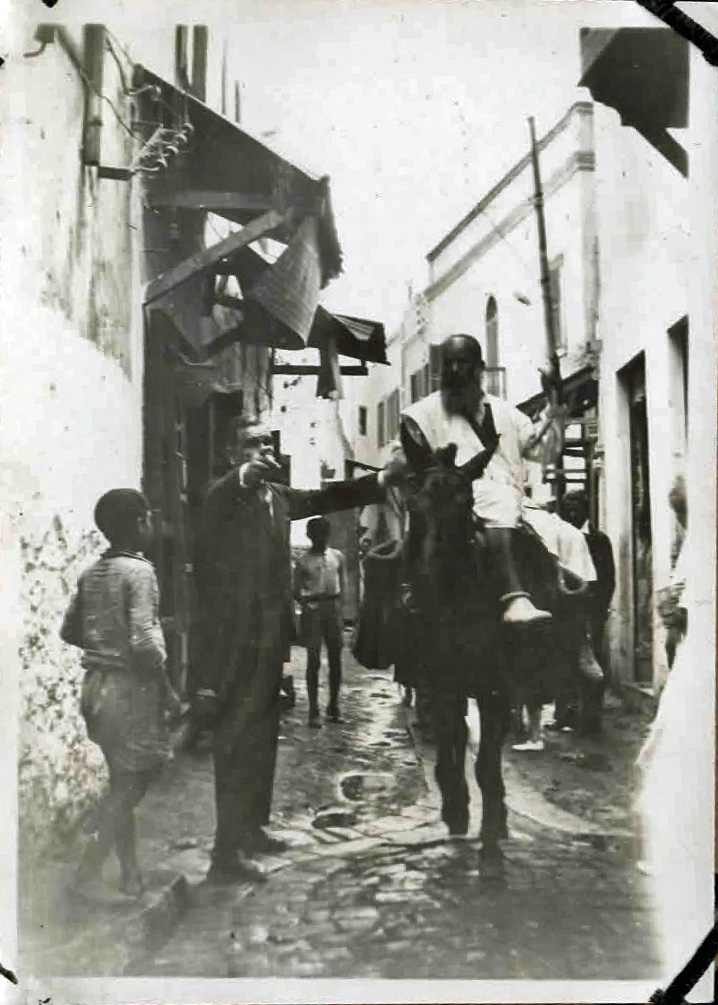 Old photo of street with man on a donkey