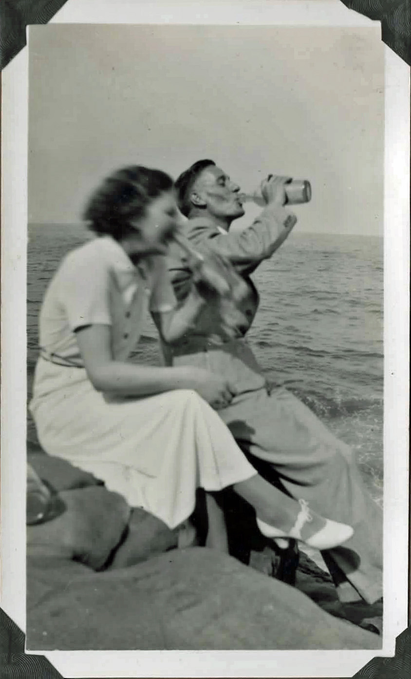 Old photo of a couple sitting on rocks by the sea