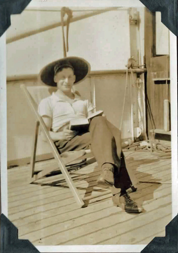 Old photo of a man on deck reading a book