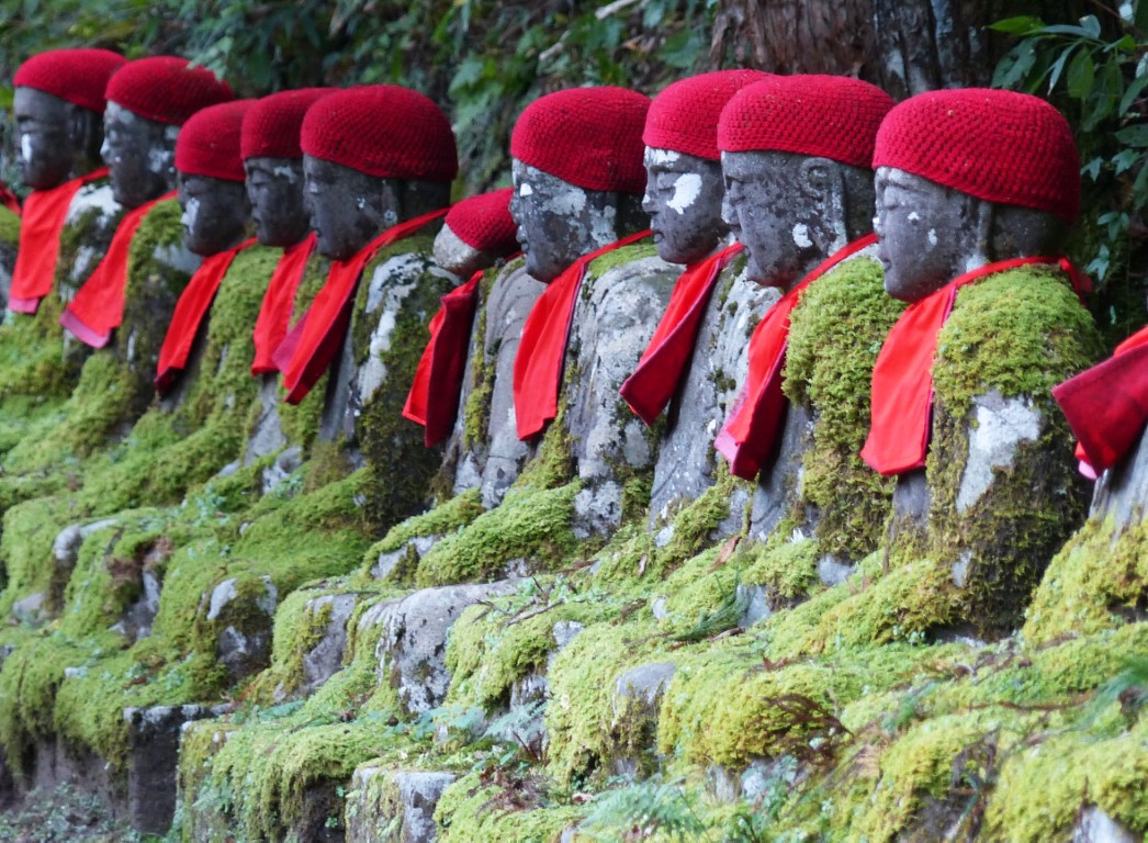 Line of seated stone statues wearing red caps and bibs