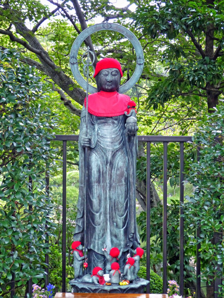 A stone statue wearing a red cap and bib, with babies at his feet