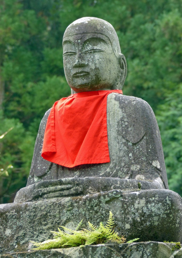 A seated stone statue wearing a red cap and bib