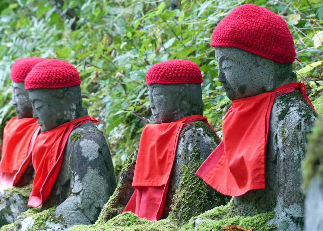 Four seated stone statues wearing red caps and bibs