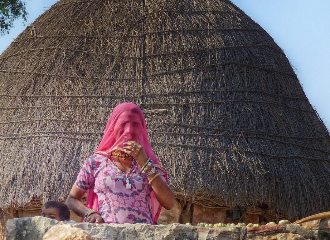 Lady in pink head covering in front of grass roof