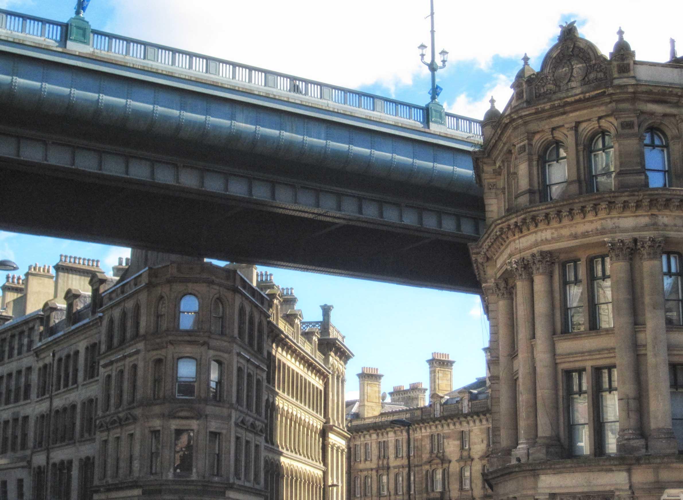 Bridge high up between old stone buildings