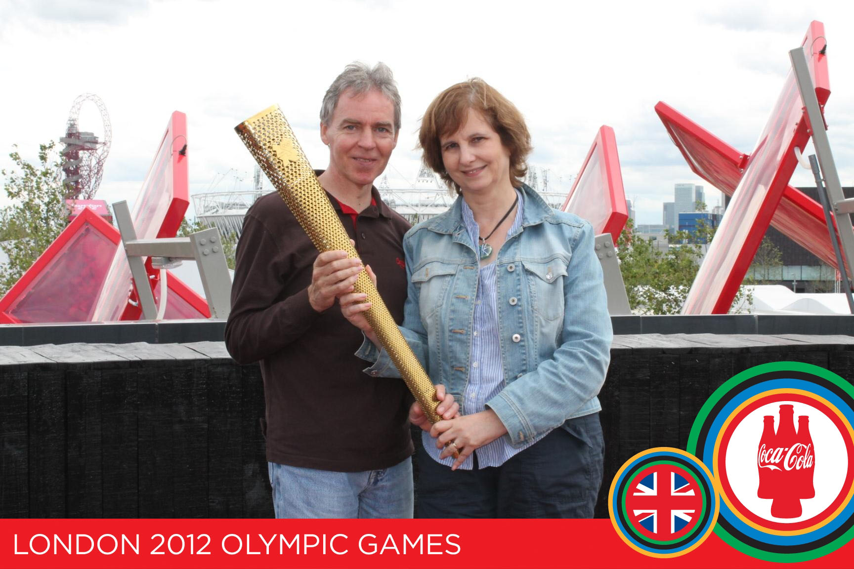 Couple posing for photo with Olympic torch