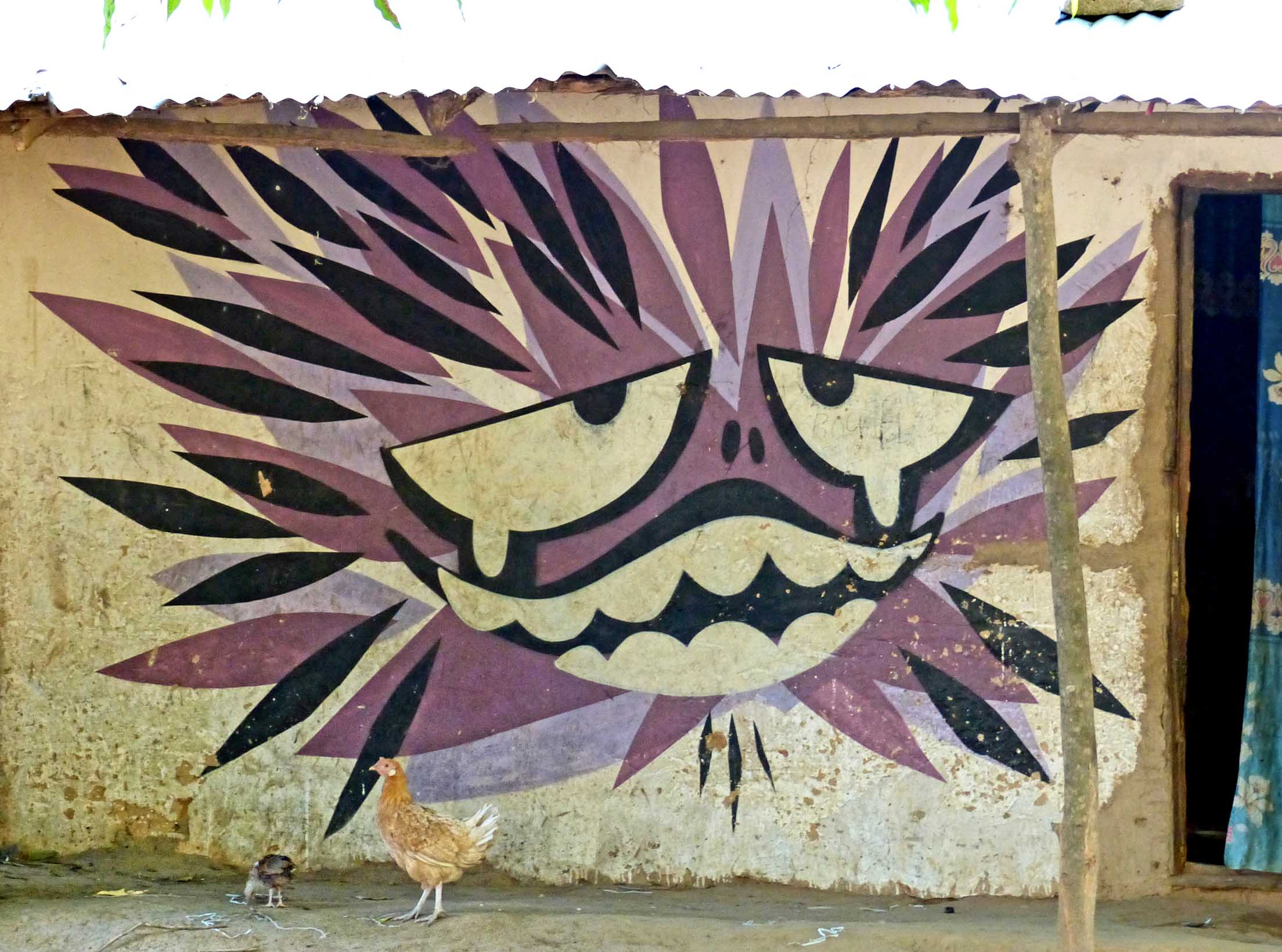 Mural of mask with chickens in front of the wall
