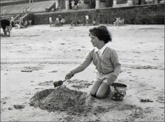 Black and white photo pf little girl making a sandcastle