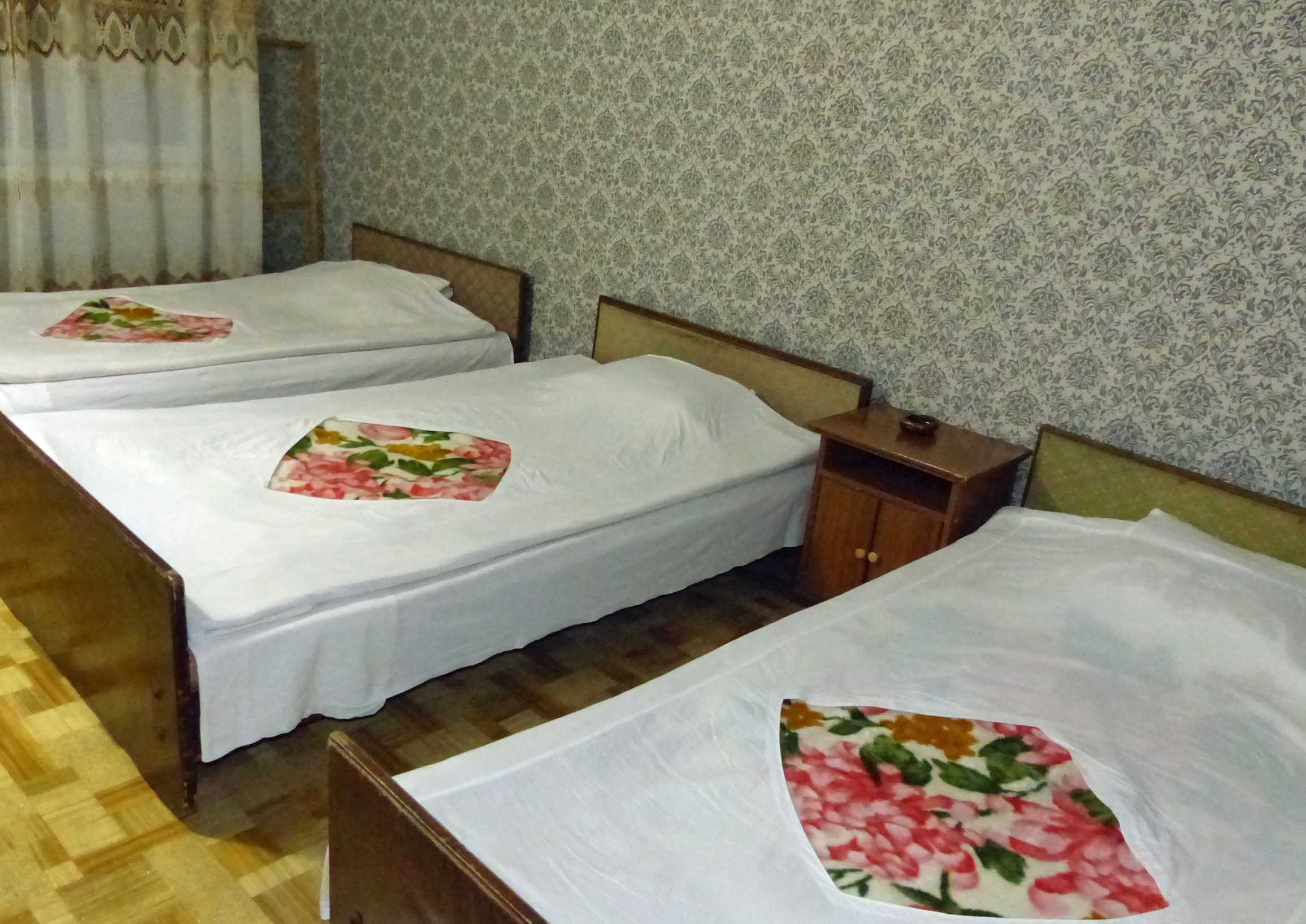 Three simple beds with floral spreads on lino floor