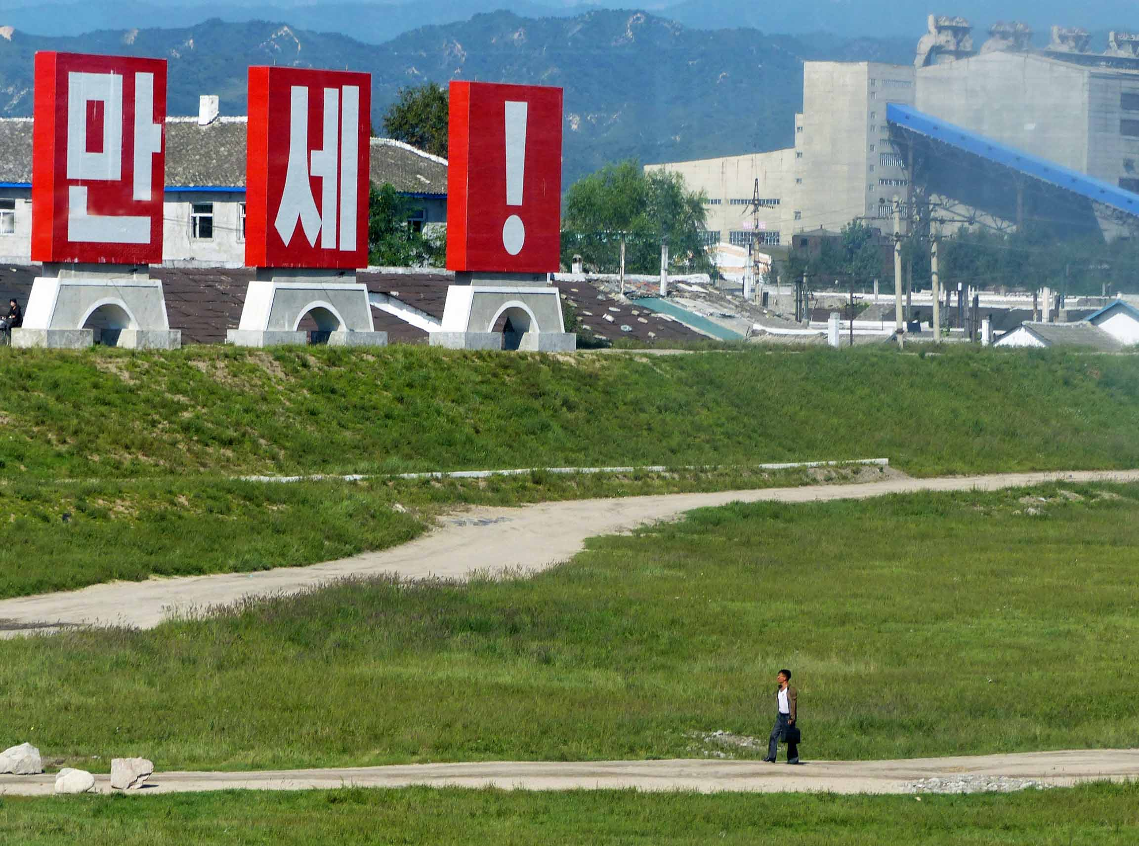 Man walking past huge red Korean characters and factories