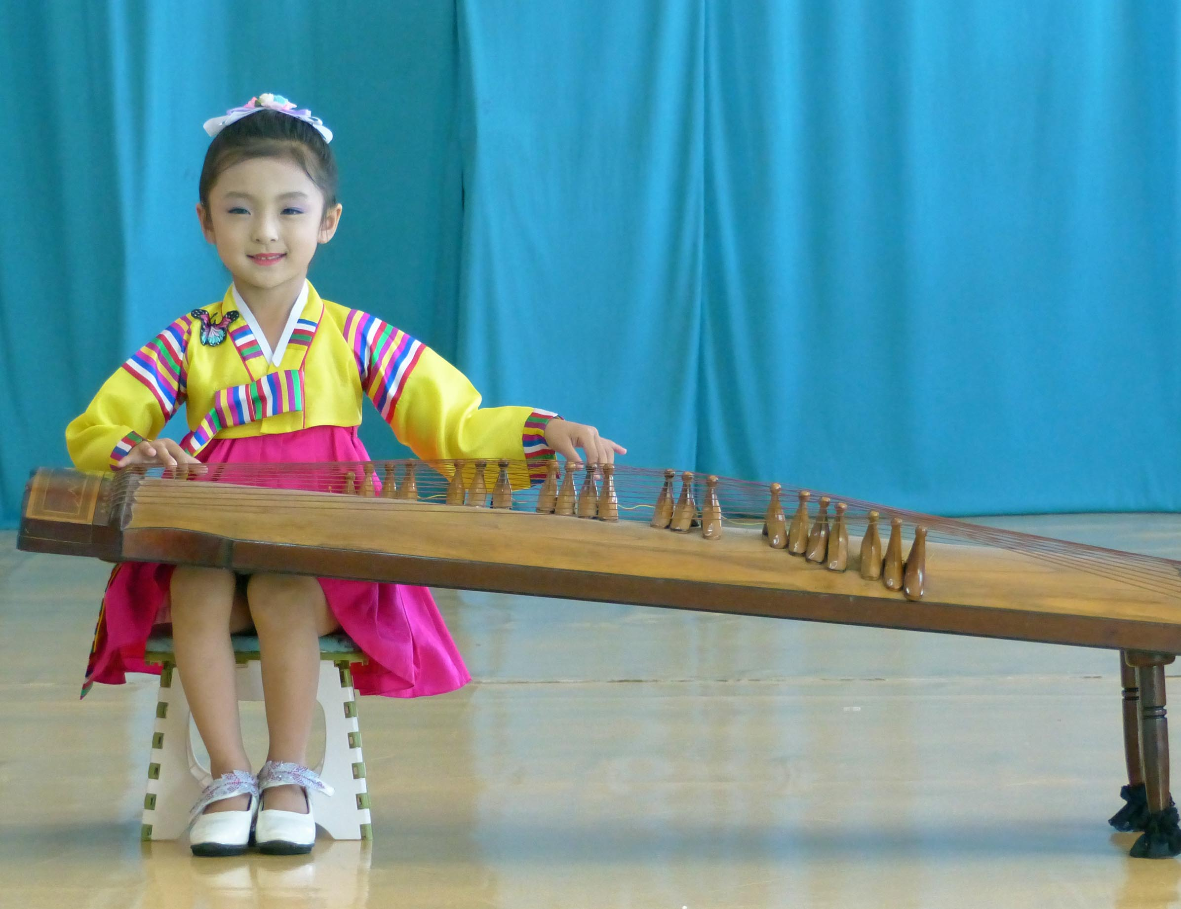 Young girl in traditional dress playing stringed instrument