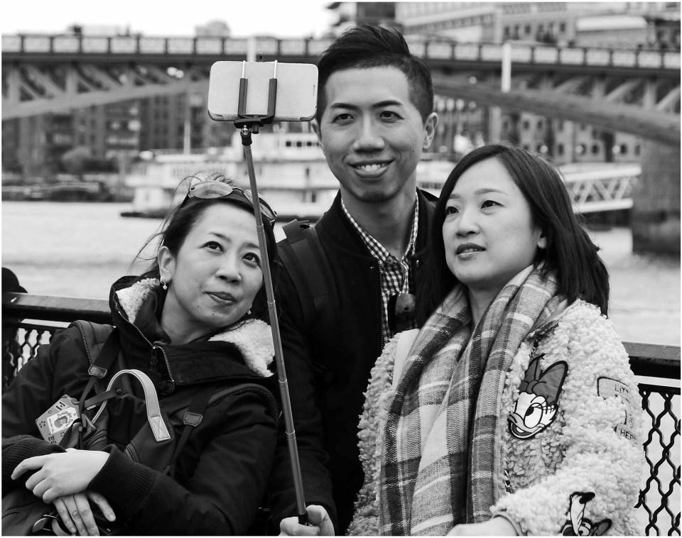 Three tourists taking photo with selfie stick