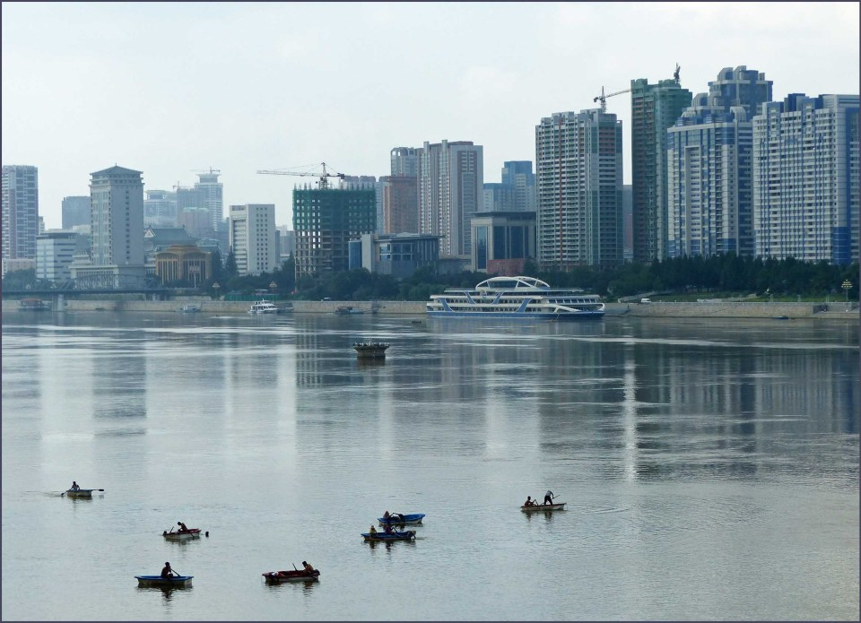 Wide river with small boats, lined with tall buildings