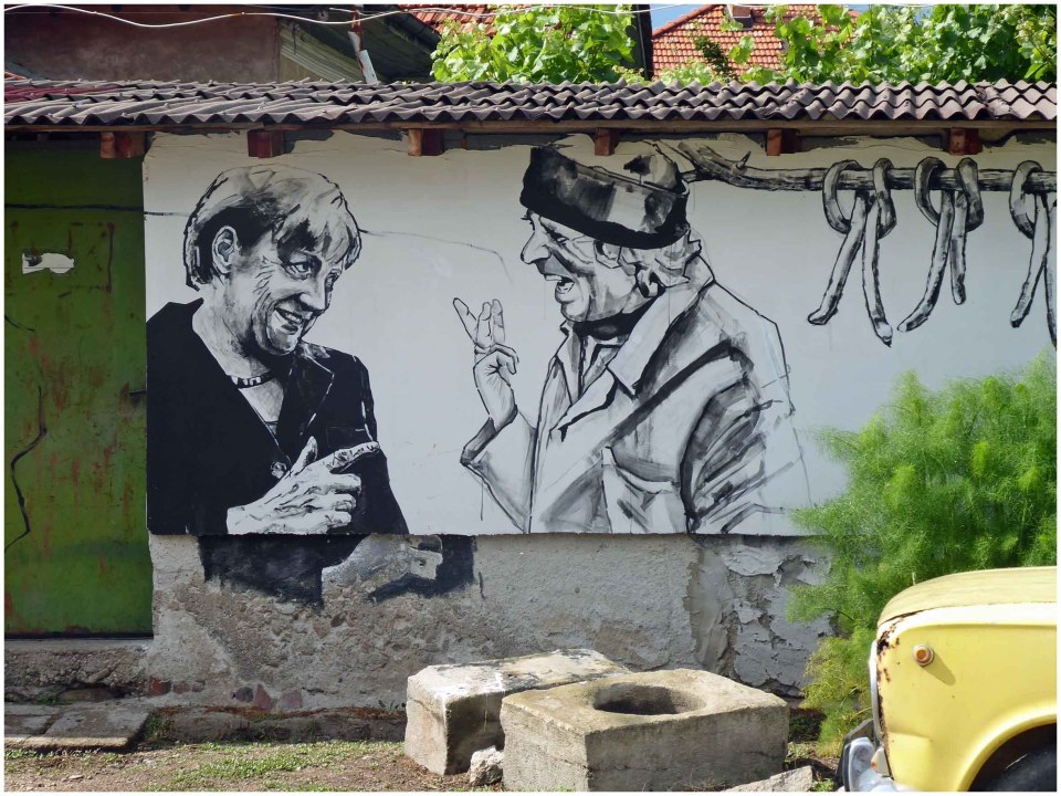 Mural of Angela Merkel and a man in a cap