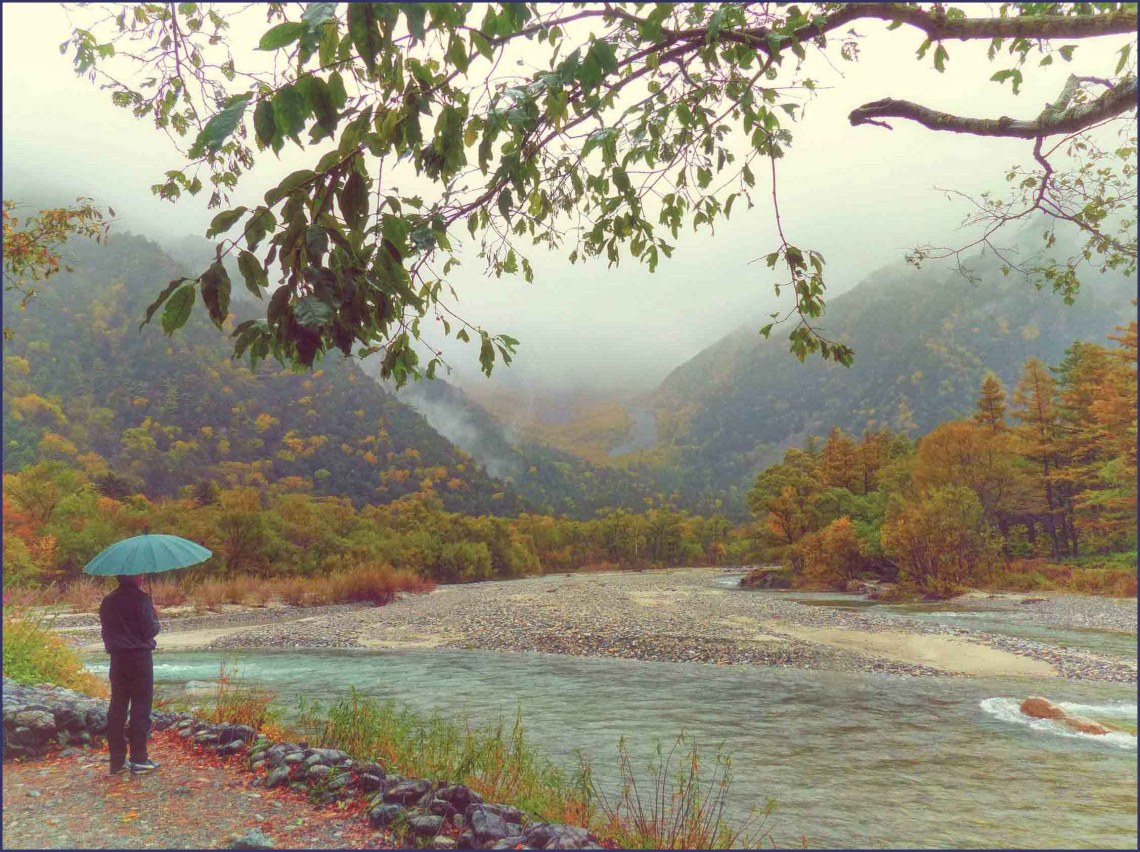 Man with green umbrella by a river in autumn